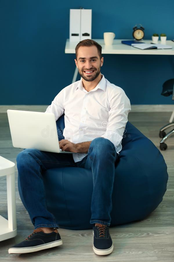 Young businessman with laptop sitting on beanbag chair in office stock images