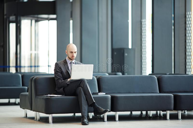 Networking in lounge. Young businessman with laptop sitting on black leather sofa in airport lounge and networking royalty free stock photos