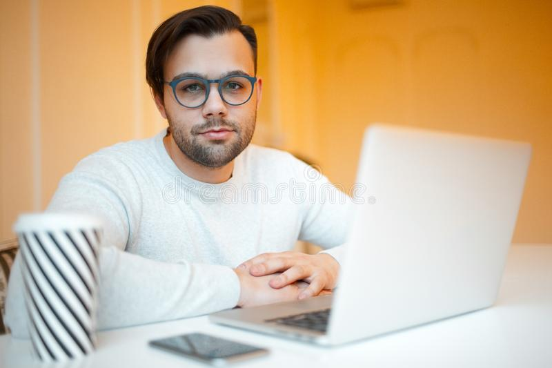 Young businessman with laptop, smartphone and coffee on white table. Wearing blue glasses and sweater, over yellow background.  royalty free stock image