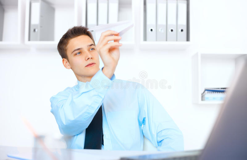 Young businessman launch a paper airplane. Portrait of young businessman launch a paper airplane at his workplace in bright office stock photos
