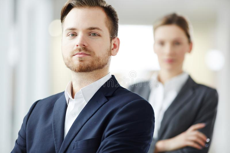 Leader and subordinate. Young businessman or leader in formalwear on background of his colleague or subordinate royalty free stock photos