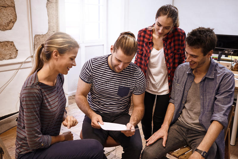 Young businessman leading by sharing ideas. Young business team sitting and standing around in a semi circle all looking thoughtfully at memorandum while one is royalty free stock photos