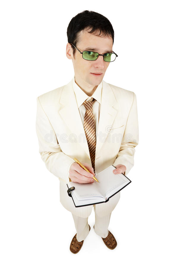 Young businessman in light suit writes in notebook stock image