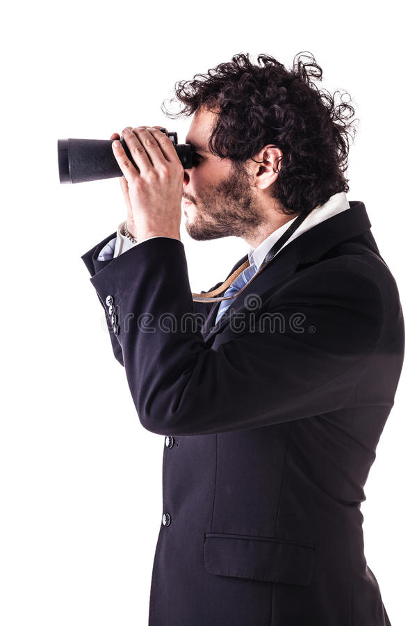 Young businessman looking through binoculars royalty free stock image