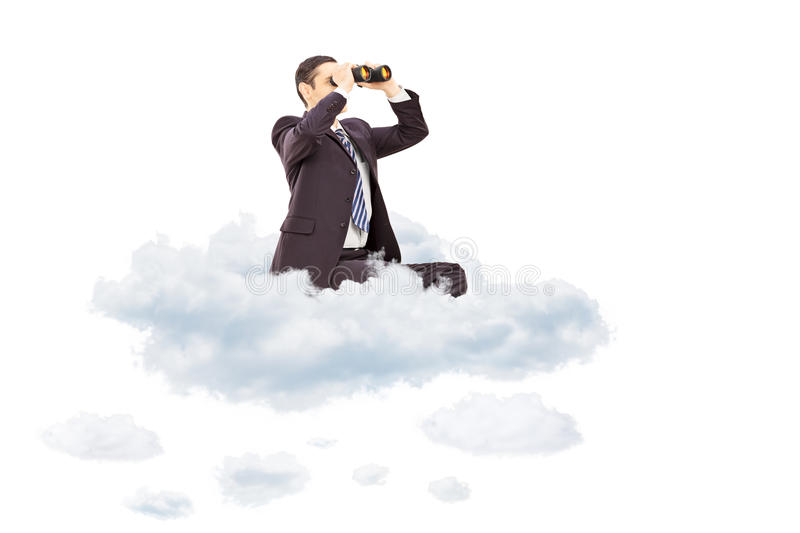Young businessman looking through binoculars seated on cloud stock photo