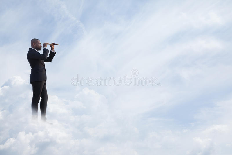 Young businessman looking through telescope in a dreamlike cloud world royalty free stock photography