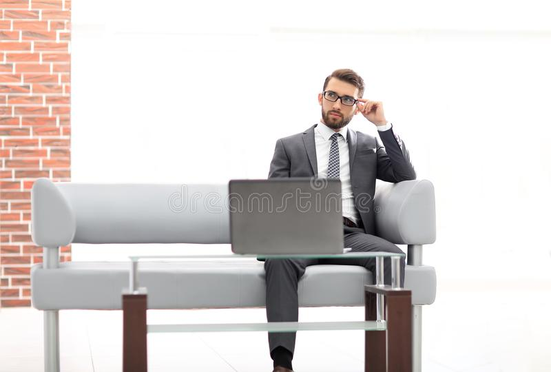 Young businessman looking to the camera wearing glasses royalty free stock image