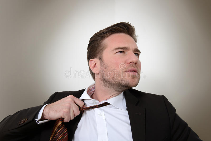 Young businessman loosening a tie. Close up of young Caucasian businessman loosening a tie stock photography
