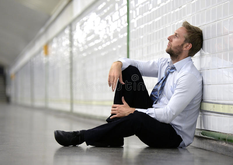Young businessman lost in depression sitting on ground street subway stock photo