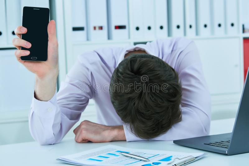 Young businessman lying on the desk in office showing blank screen of smartphone, keeping face on his hands. Deadline stock images
