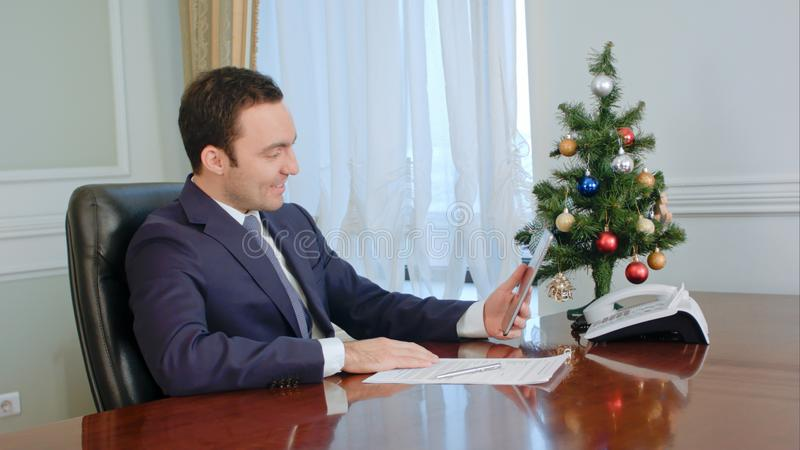 Young businessman makes call by tablet, smiling, congratulates with Christmas royalty free stock photography