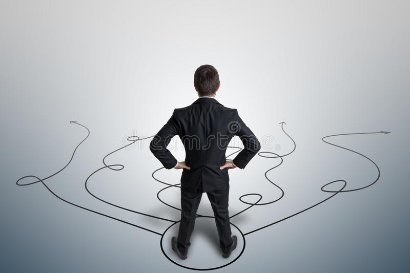 Young businessman is making decision and selecting strategy. View from behind stock images