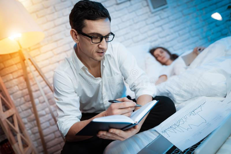 Young businessman is making notes in black notepad on the bed. Young woman is sleeping next to man and is holding book. royalty free stock photography