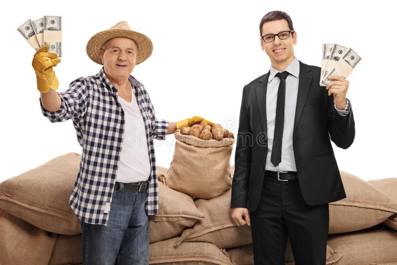 Young businessman and mature farmer holding money bundles. In front of a pile of burlap sacks isolated on white background stock images