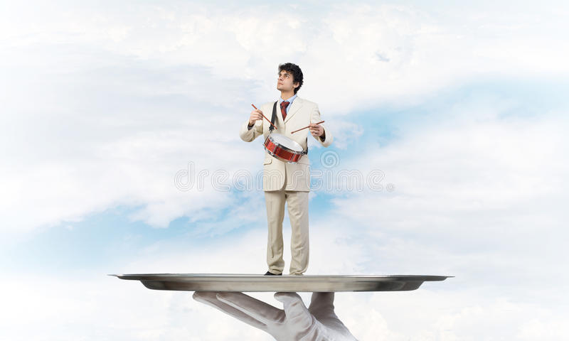 Young businessman on metal tray playing drums against blue sky background. Hand of waiter presenting on tray man playing drums royalty free stock photos