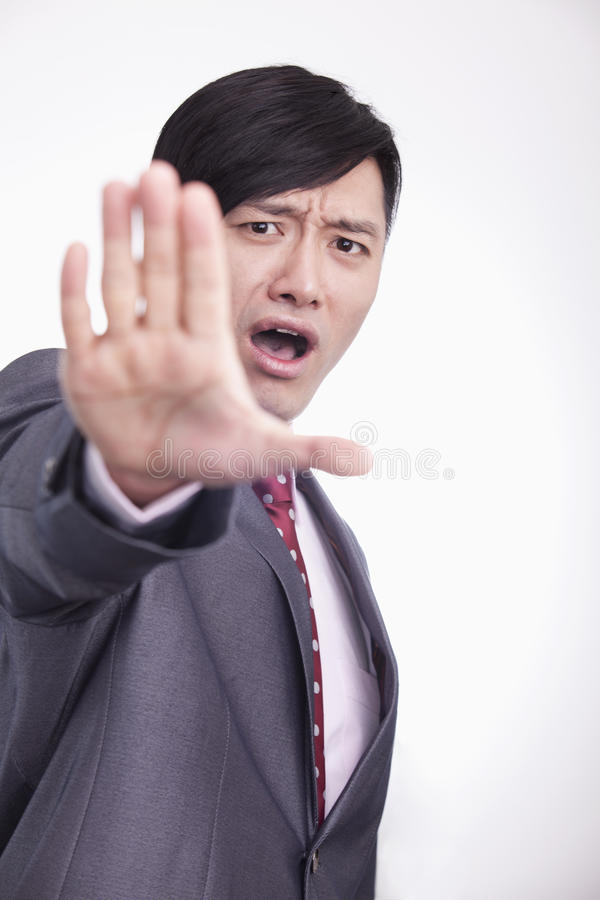 Young Businessman With Mouth Open And Hand Raised In Stop Gesture, Studio Shot Royalty Free Stock Image