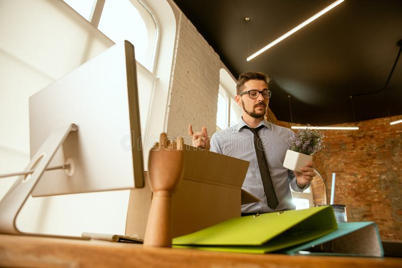 A young businessman moving in office, getting new work place stock image