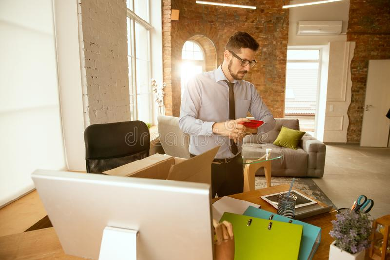 A young businessman moving in office, getting new work place royalty free stock photo