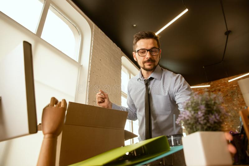 A young businessman moving in office, getting new work place stock photos