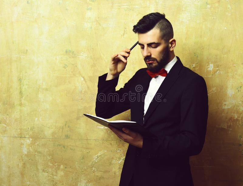 Young businessman with neat beard and haircut reading organizer stock photo