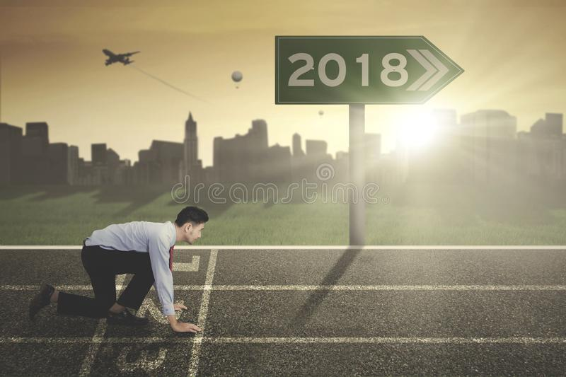 Young businessman with numbers 2018 on the signpost. Young businessman kneeling on the start line with numbers 2018 on the signpost. Shot at sunrise time stock image