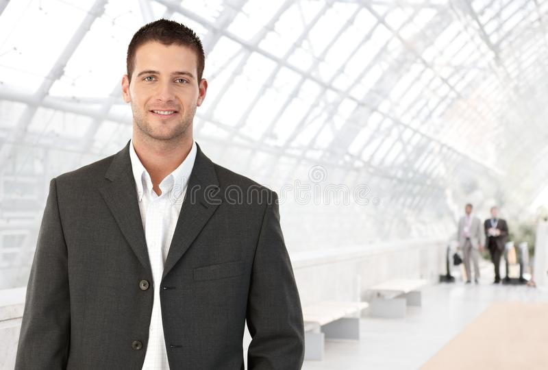 Young businessman in office lobby. Young businessman standing in bright office lobby smiling at camera stock image