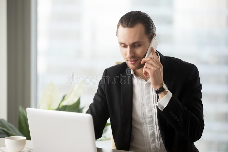 Young businessman in office looking at laptop making phone call. stock photo
