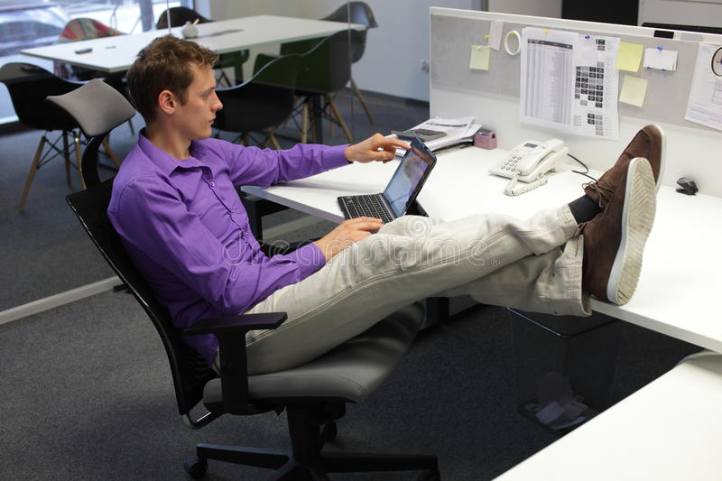 Young businessman in office with tablet - relaxed sitting position. Young businessman caucasian in his office working with tablet - relaxed sitting position with stock image