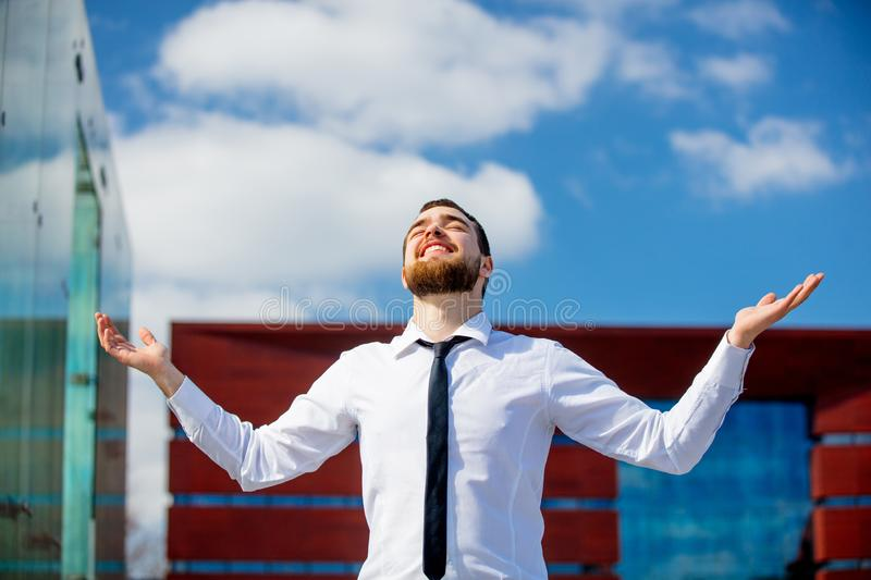 Young businessman with open arms at city outdoor. With business building on background royalty free stock photography