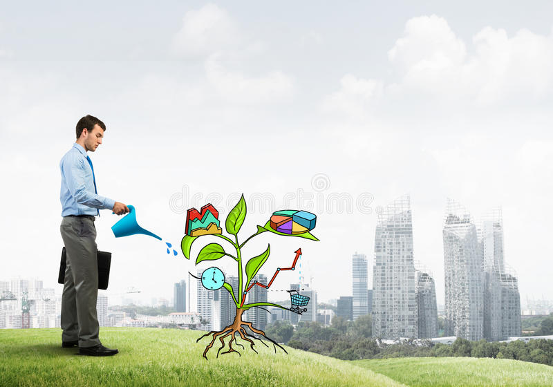 Young businessman outdoors watering drawn growth concept with can. Handsome businessman presenting investment and financial growth concept stock photos