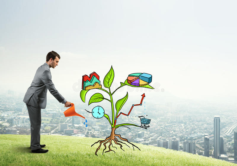 Young businessman outdoors watering drawn growth concept with can. Handsome businessman presenting investment and financial growth concept royalty free stock image
