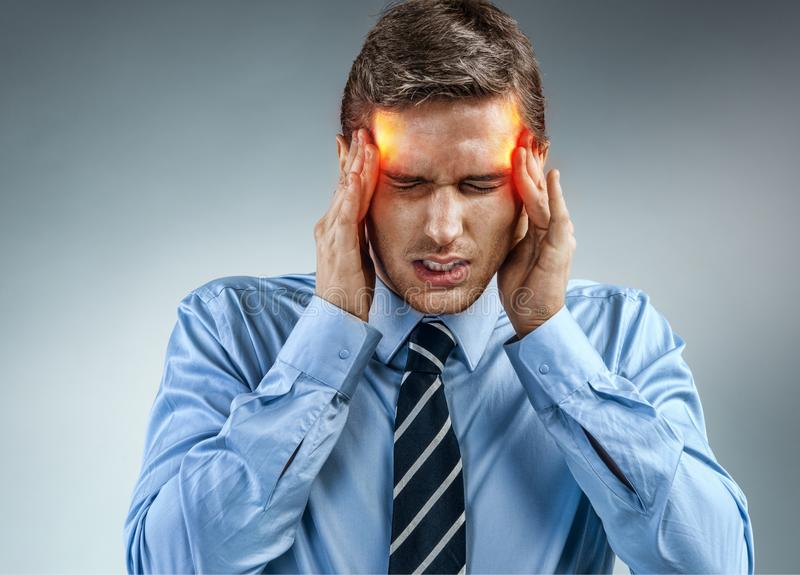 Young businessman with pain in his temples. royalty free stock photos