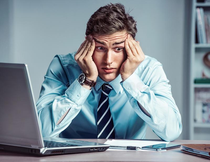 Young businessman with pain in his temples. stock photo