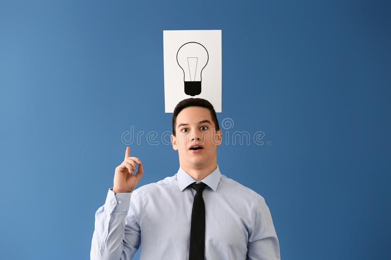 Young businessman and paper sheet with drawn light bulb as symbol of idea on color background stock images