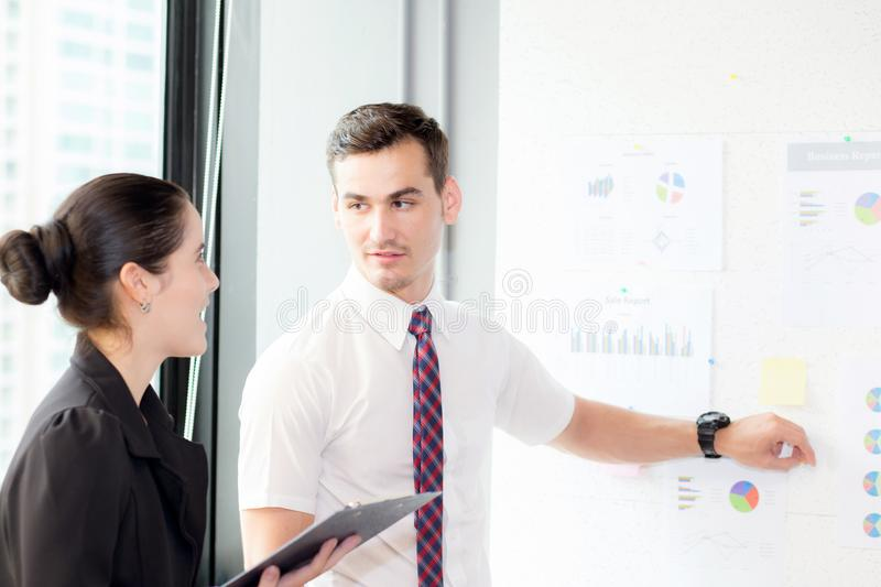 Young businessman pointing towards graph and businesswoman holding clipboard with present profit while giving presentation. In office, teamwork concept royalty free stock photo