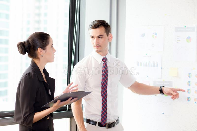 Young businessman pointing towards graph and businesswoman holding clipboard with present profit while giving presentation. In office, teamwork concept royalty free stock photos