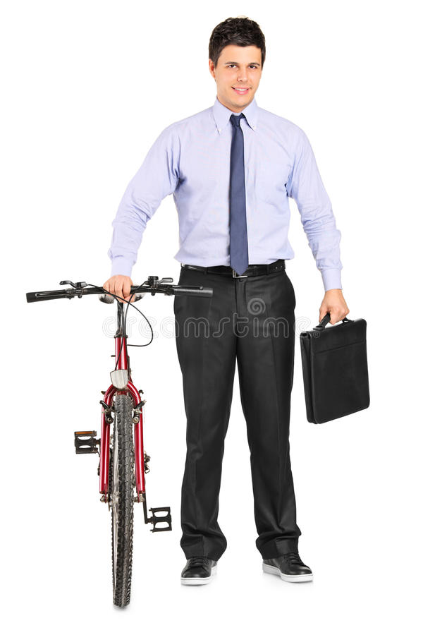 Young businessman posing next to a bicycle