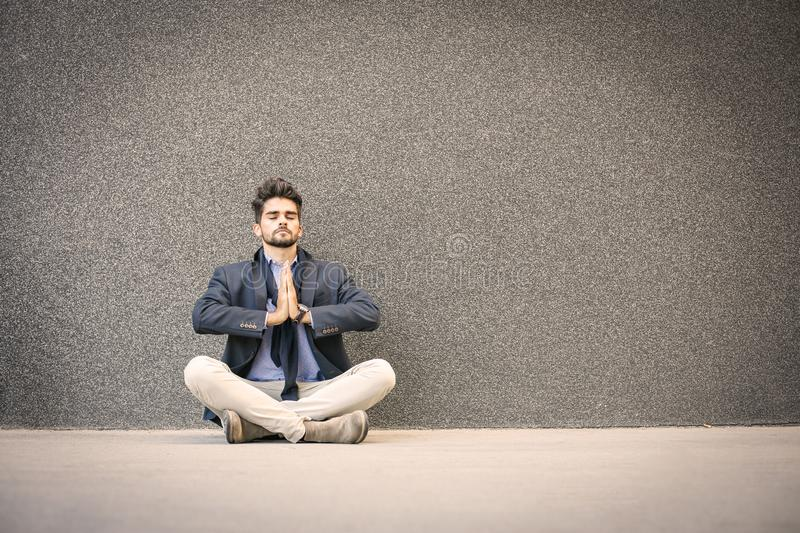 Businessman practicing yoga on the street. Space for copy. royalty free stock photography
