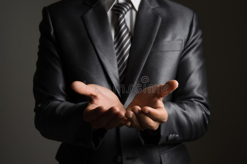 Young businessman presenting a copyspace isolated on black background. stock photography