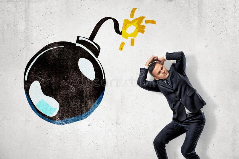 Young businessman protecting his head with his hands and big cartoon ball bomb on white background royalty free illustration