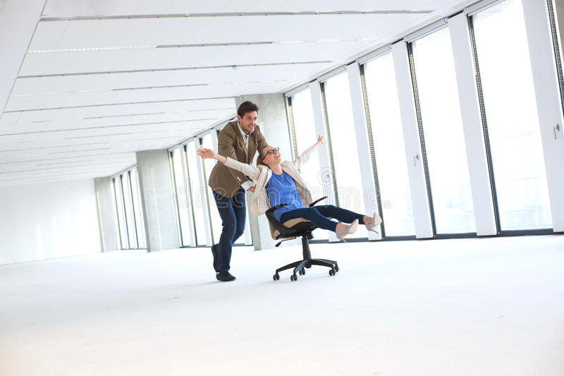 Young businessman pushing female colleague in chair at empty office stock images