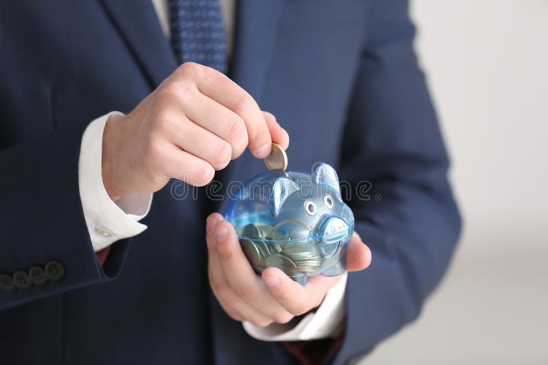 Young businessman putting coin into piggy bank on light background, closeup. Money savings concept stock images