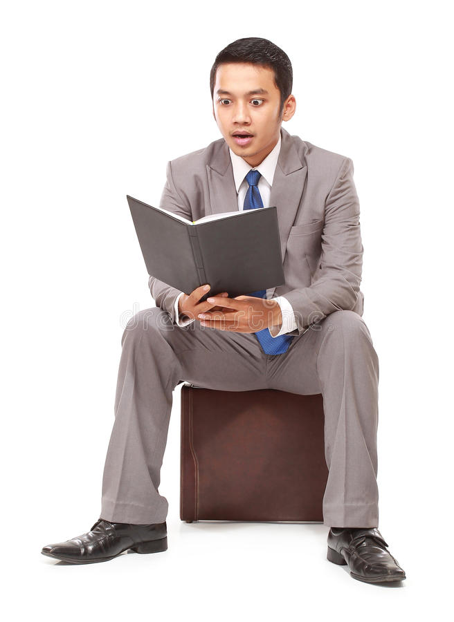 Young businessman reading a book and surprised royalty free stock photos