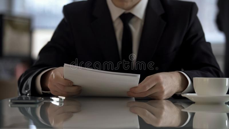 Young businessman reading terms of agreement for signing, business contract royalty free stock images