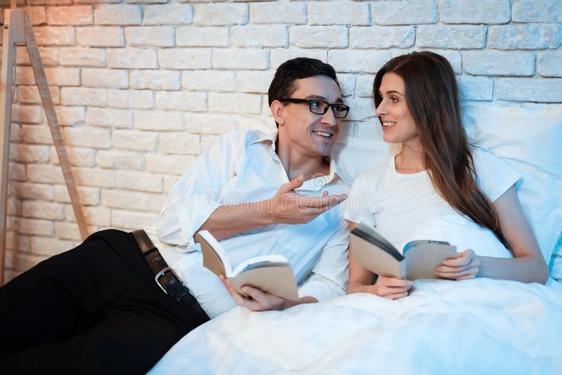 Young businessman reads book in bed with his white woman. Man and woman lying in bed at home. stock photos