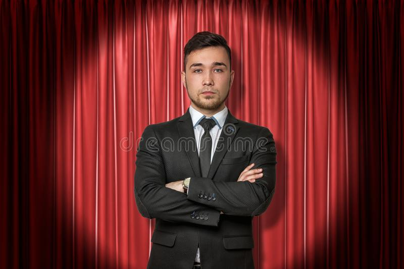 Young businessman on red stage curtains background stock photography