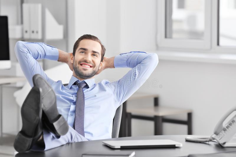 Young businessman relaxing office stock image