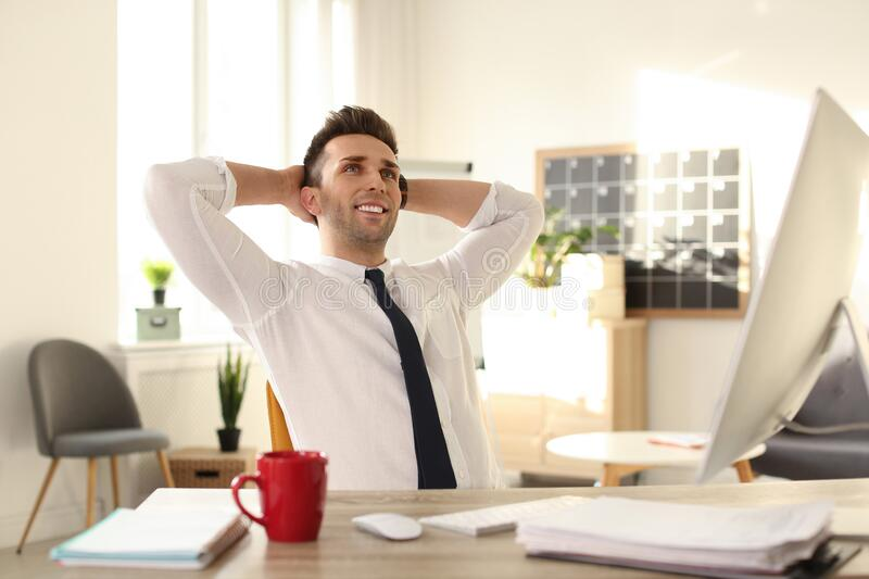 Young businessman relaxing at table in office royalty free stock images