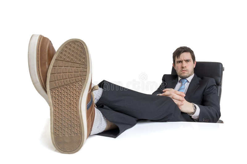 Young businessman is relaxing at workplace and has his feet on desk. Isolated on white background stock photos