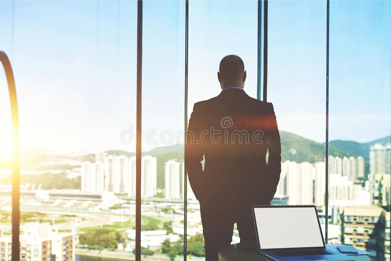 Young businessman is resting after hard work day. Back view of man in suit is watching in window on a buildings what built his construction company and behind royalty free stock image